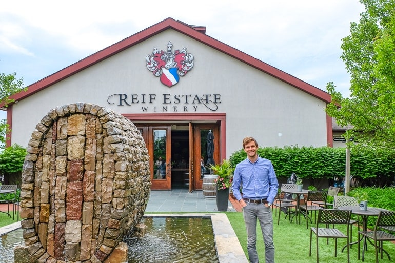 man standing beside fountain in front of winery entrance reif estates