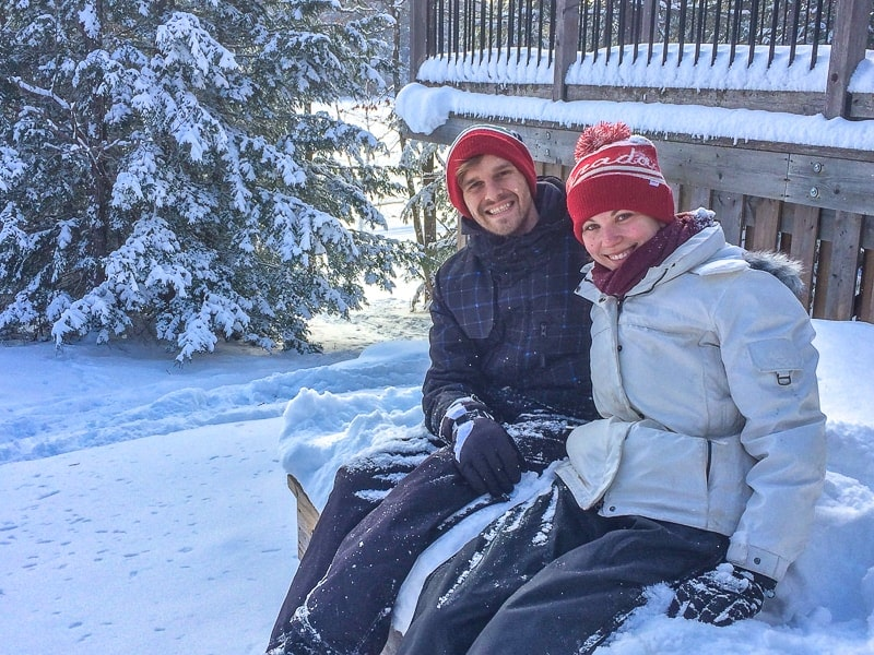 young couple in jackets sitting in heavy snow ontario away travel