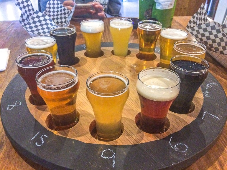 sample craft beer in glasses in wooden wheel on table sawdust brewery ontario