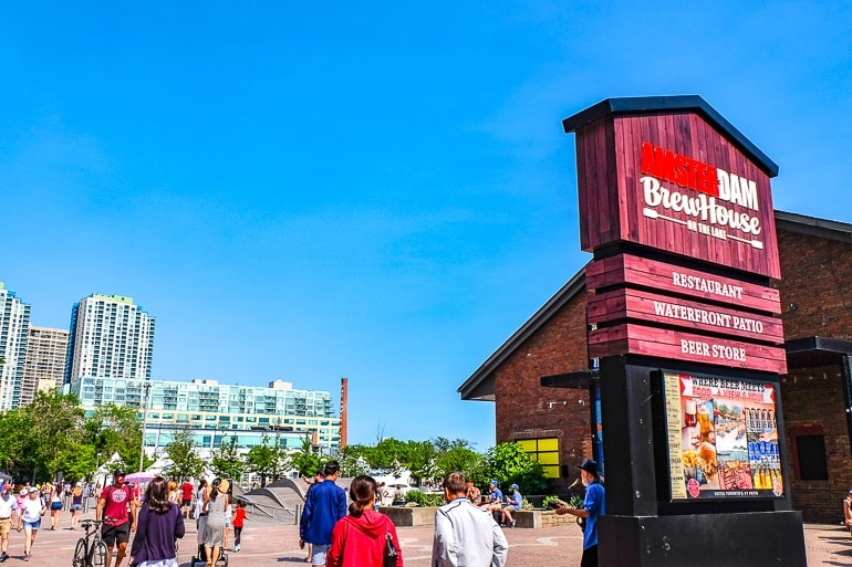red brewery sign at lake front with people behind harbourfront toronto attractions