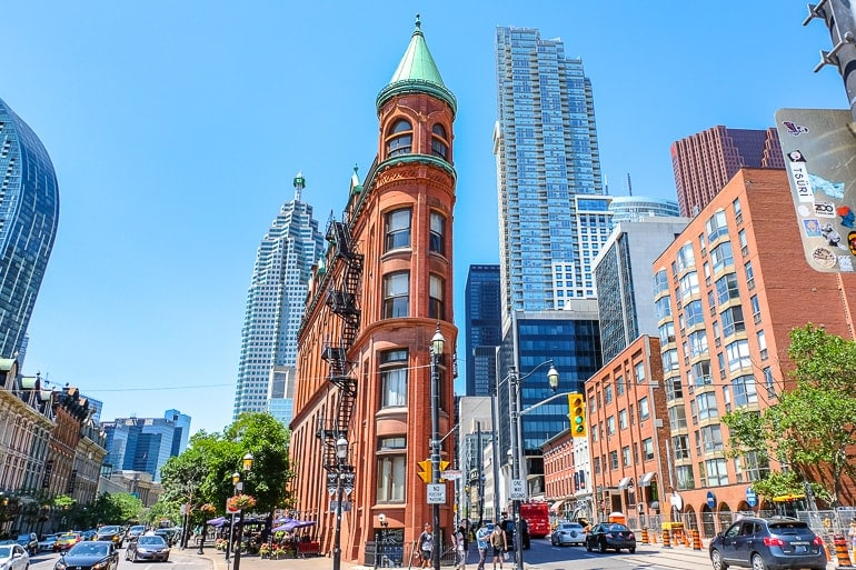 red brick building with green cone top at street intersection toronto tourist attraction flatiron building