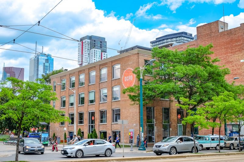 orange brick hotel ocho building with cars and trees in downtown toronto