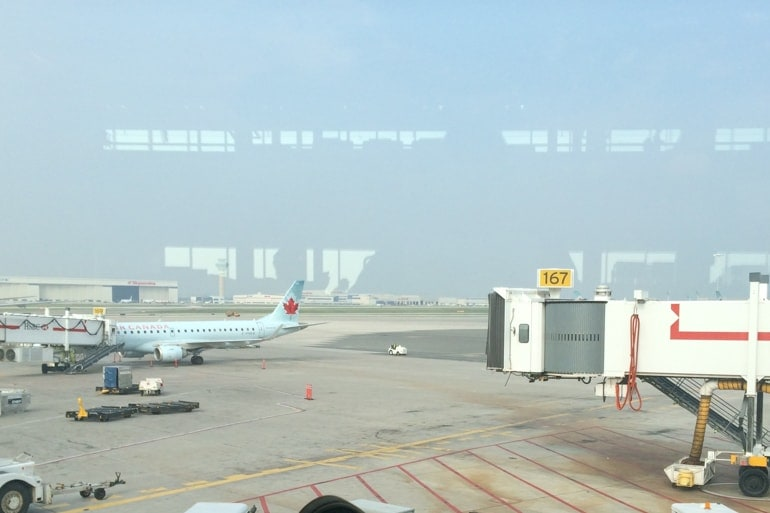 airplane and tunnel on tarmac through window at pearson airport