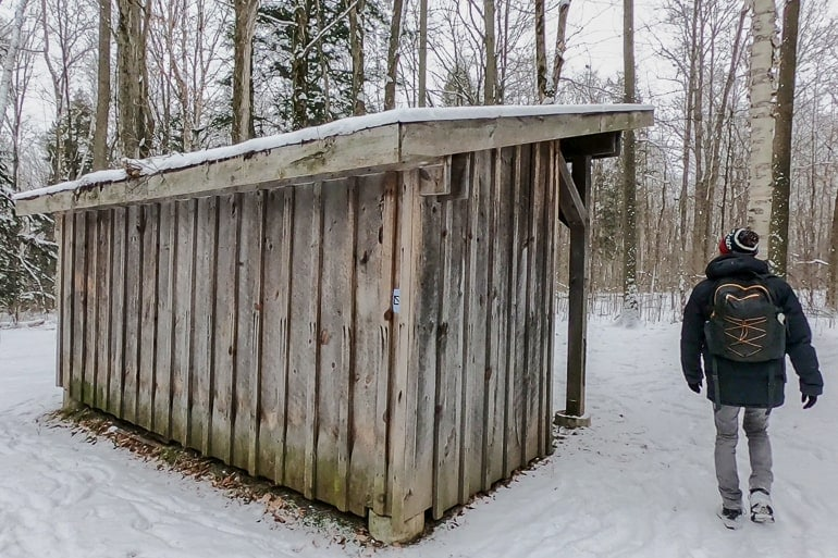 wooden shed with man walking beside in snow scanlon creek conservation area