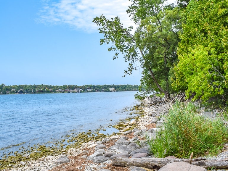 blue lake water and shoreline with green trees things to do in kingston ontario conservation area