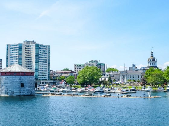 city waterfront with stone tower and boats docked at piers things to do in kingston ontario