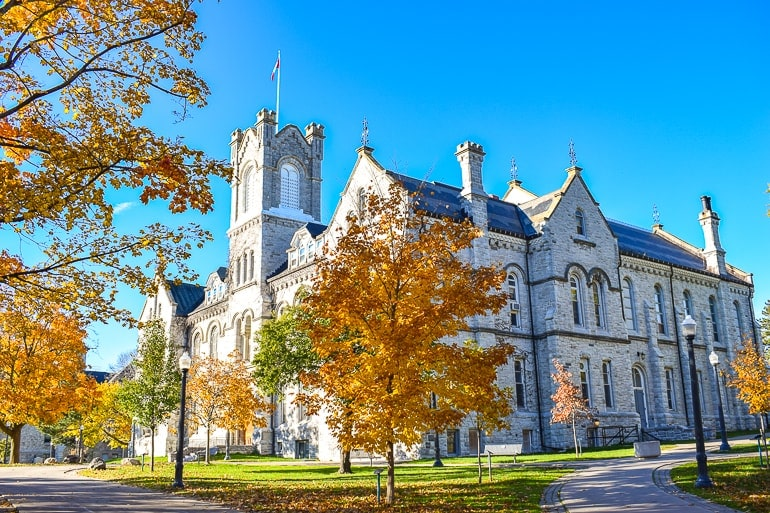 old limestone building with autumn trees things to do in kingston ontario queens university