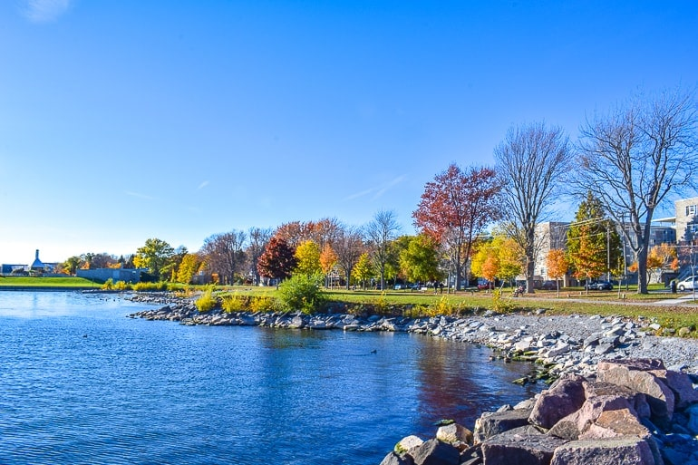 waterfront path with rocky shore and autumn trees things to do in kingston ontario