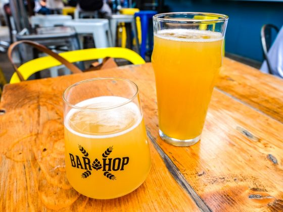 two pints of orange beer on wooden table bar hop bars in downtown toronto