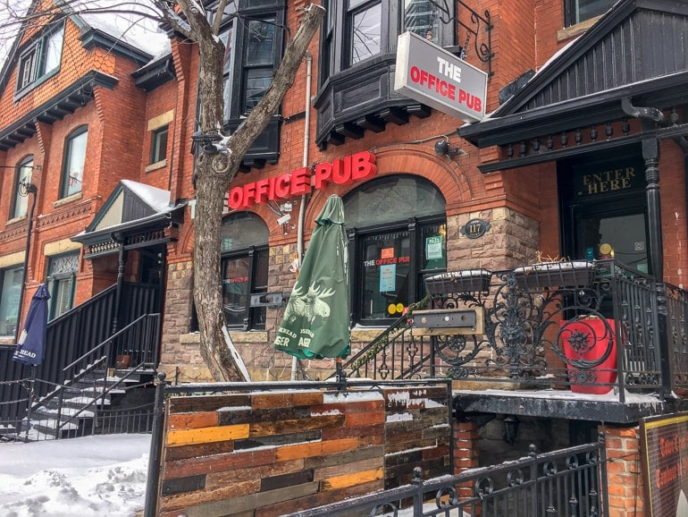bar entrance in brick building with red sign and patio bars in downtown toronto