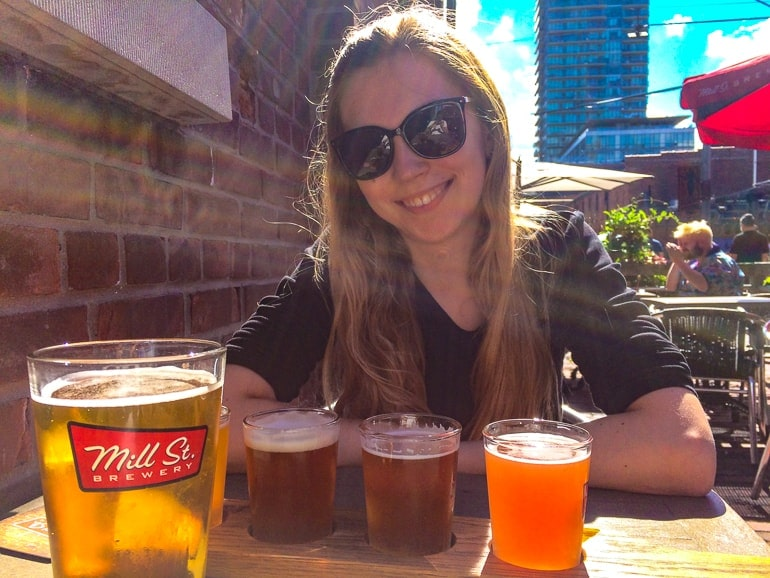 small pints of beer on table with woman behind one day in toronto