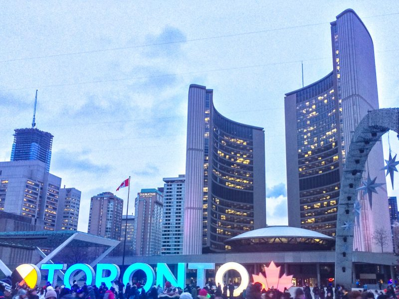 large buildings in Toronto behind ice skaters in front