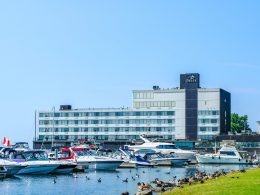 steel hotel on waterfront with boats in front and blue sky places to stay in kingston ontario