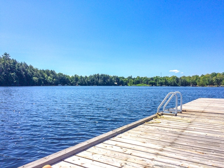 blue lake with wooden dock an blue sky cottage rental