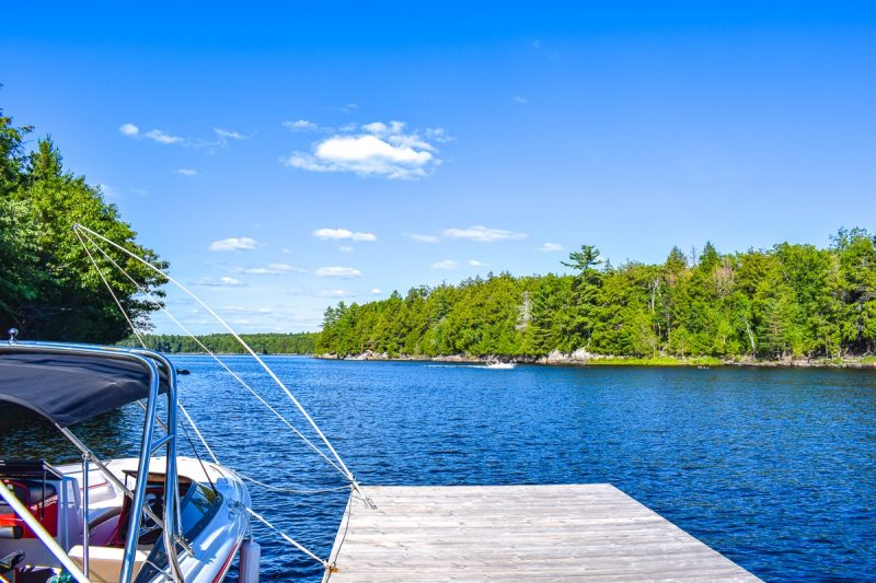 dock with boat and blue lake and trees cottage rentals in ontario