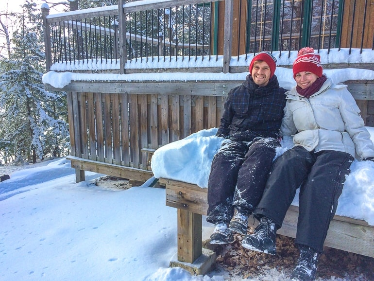 man and woman in snow gear sitting in snow cottage rentals ontario