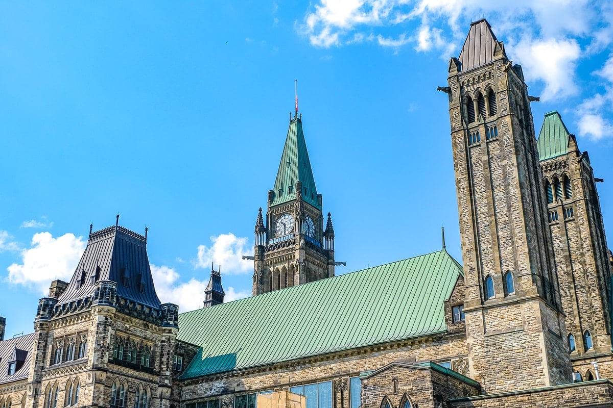 tall clock tower and buildings with blue sky toronto to ottawa
