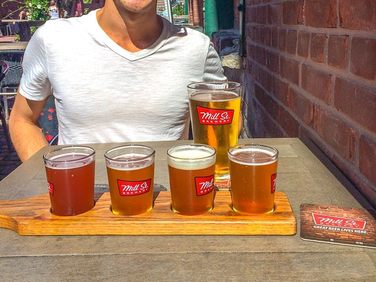 flights of beers on table with man visiting toronto