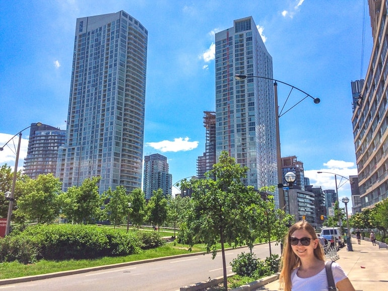 city skyscrapers with green park and girl walking on sidewalk visiting toronto