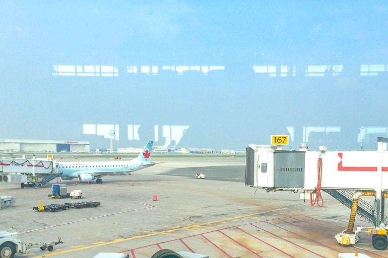 airplane on tarmac through glass pearson airport visiting toronto