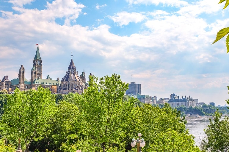 canadian parliament building with green trees in front and river below in ottawa canada