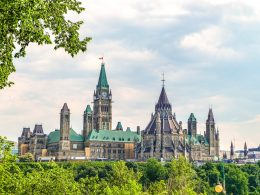 tower of canadian parliament building in distance with trees in front things to do in ottawa