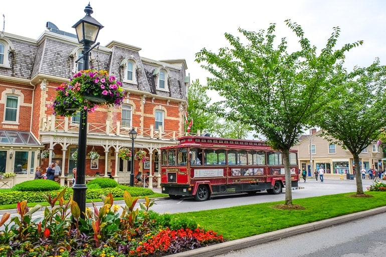 red trolley in front of old hotel with gardens niagara on the lake wine tours