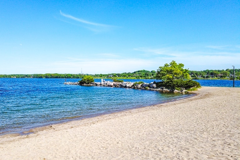 rocky point extending from beach with blue sky and water kempenfelt bay barrie