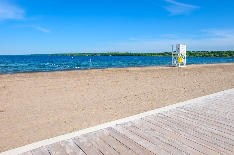 sandy beach from wooden boardwalk with lifeguard stand and blue sky