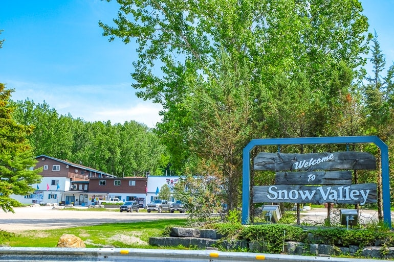 wooden entrance sign with chalet behind in forest snow valley ski ontario
