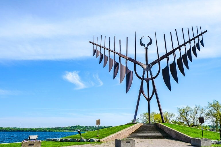 metal sculpture with wings near waterfront