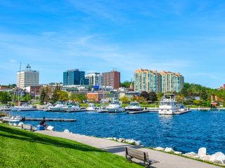 city buildings with blue sky and waterfront in front things to do in barrie ontario