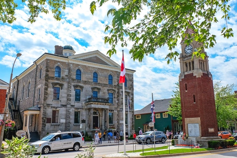 old town hall with brick cenotaph and cars on the street niagara on the lake downtown
