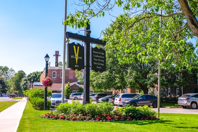 green sign for hotel inn with gardens on property niagara on the lake pillar and post