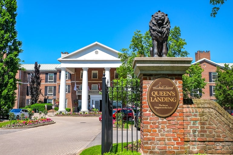 red brick gate to large hotel with white column entrance behind at queens landing
