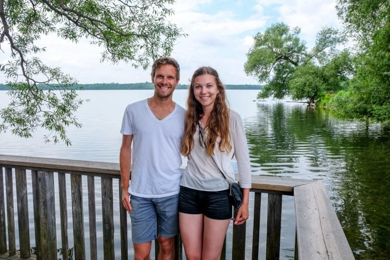 guy and girl wearing white standing in front of lake in ontario away travel blog