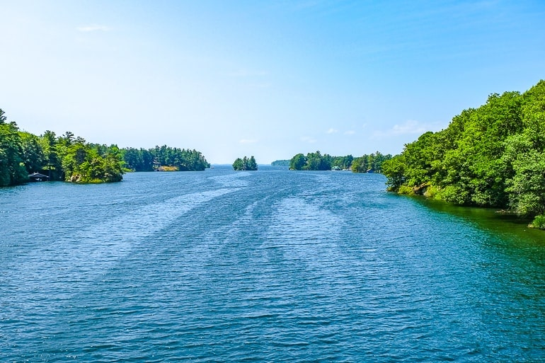 blue water with green trees on rocky islands on each side in the 1000 islands region