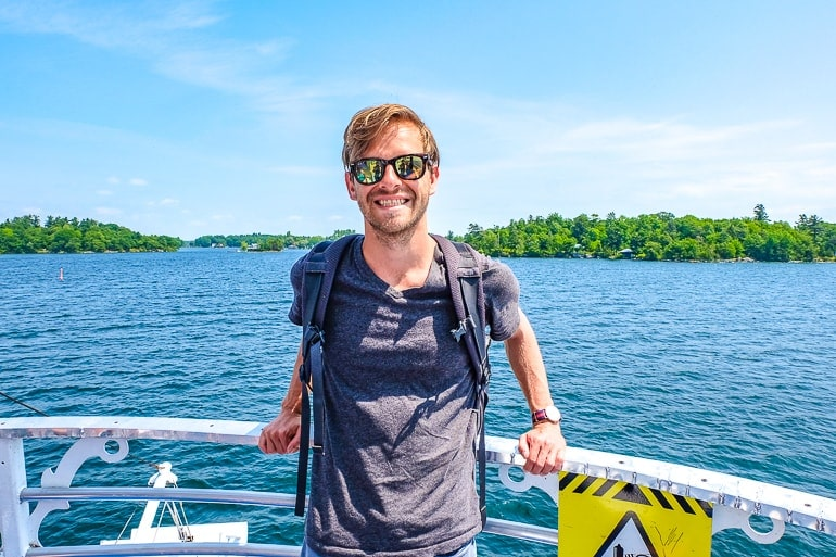 man in tshirt with sunglasses at front of boat and water behind on thousand islands cruise