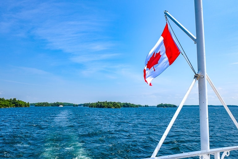 canada flag on white pole flying off back of boat with blue water below thousand island cruise
