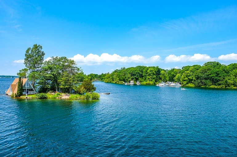 cottage on island with green trees with blue water around while on thousand islands boat tour