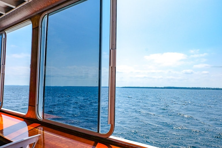 large open window with blue lake water outside thousand islands cruise