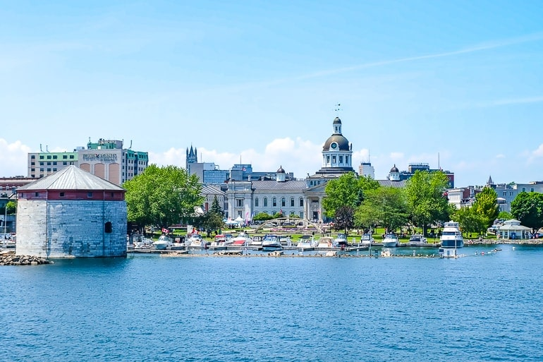 stone tower with city hall and boats at city waterfront kingston on thousand islands cruise