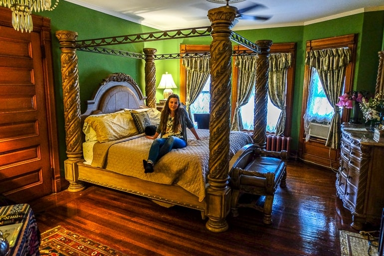 girl sitting on large king bed in antique room in niagara falls bed and breakfast