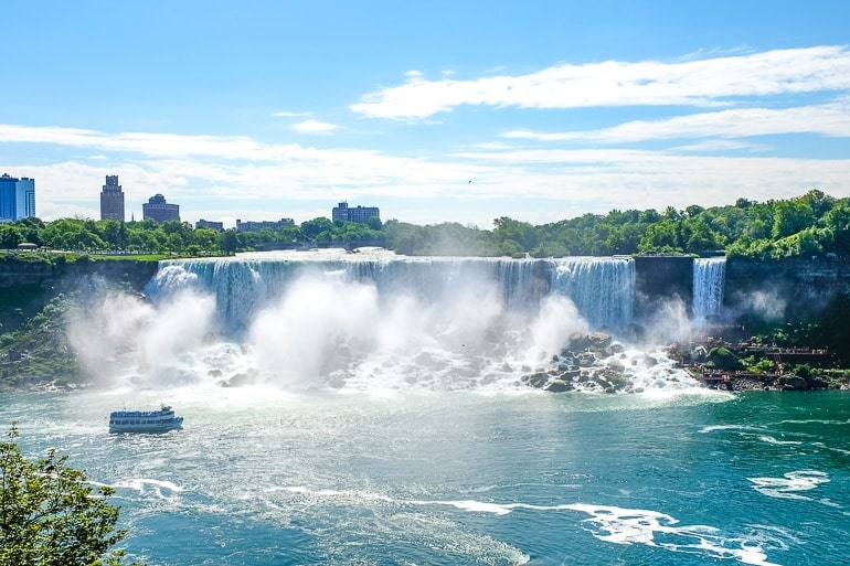 large waterfall with boat in front where to stay in niagara falls accommodations