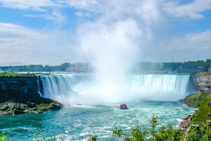 blue water over falls with small boat in river where to stay in niagara falls accommodations