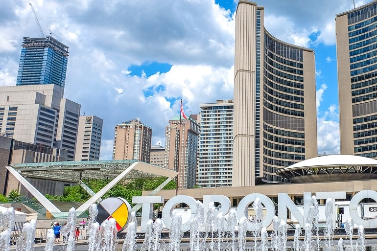 tall curved building with fountain and city sign in front in toronto with doubletree hotel behind