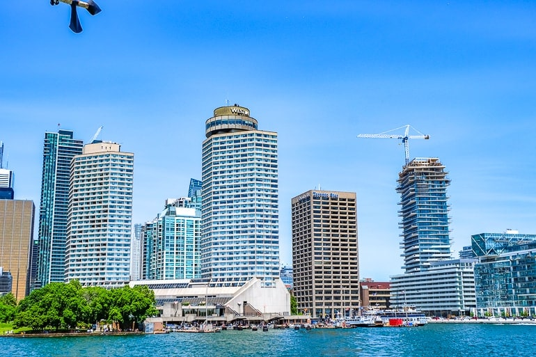 tall glass buildings at city harbourfront with lake water in toronto