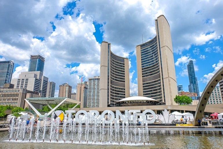 tall curved city hall buildings with fountain at base in toronto canada