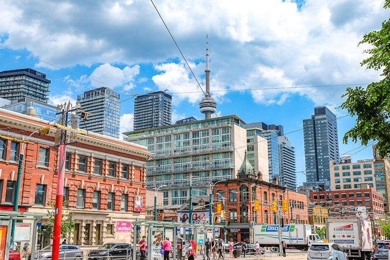 busy city intersection with people and cars and skyscrapers for where to stay in toronto