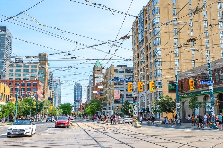 busy city intersection with cars and streetcar cables where to stay in toronto fashion district